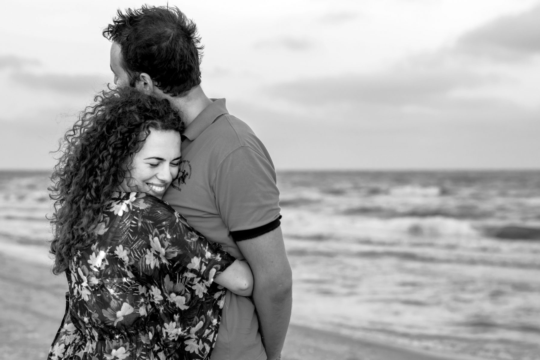 couple hugging for a beach engagement photo shoot