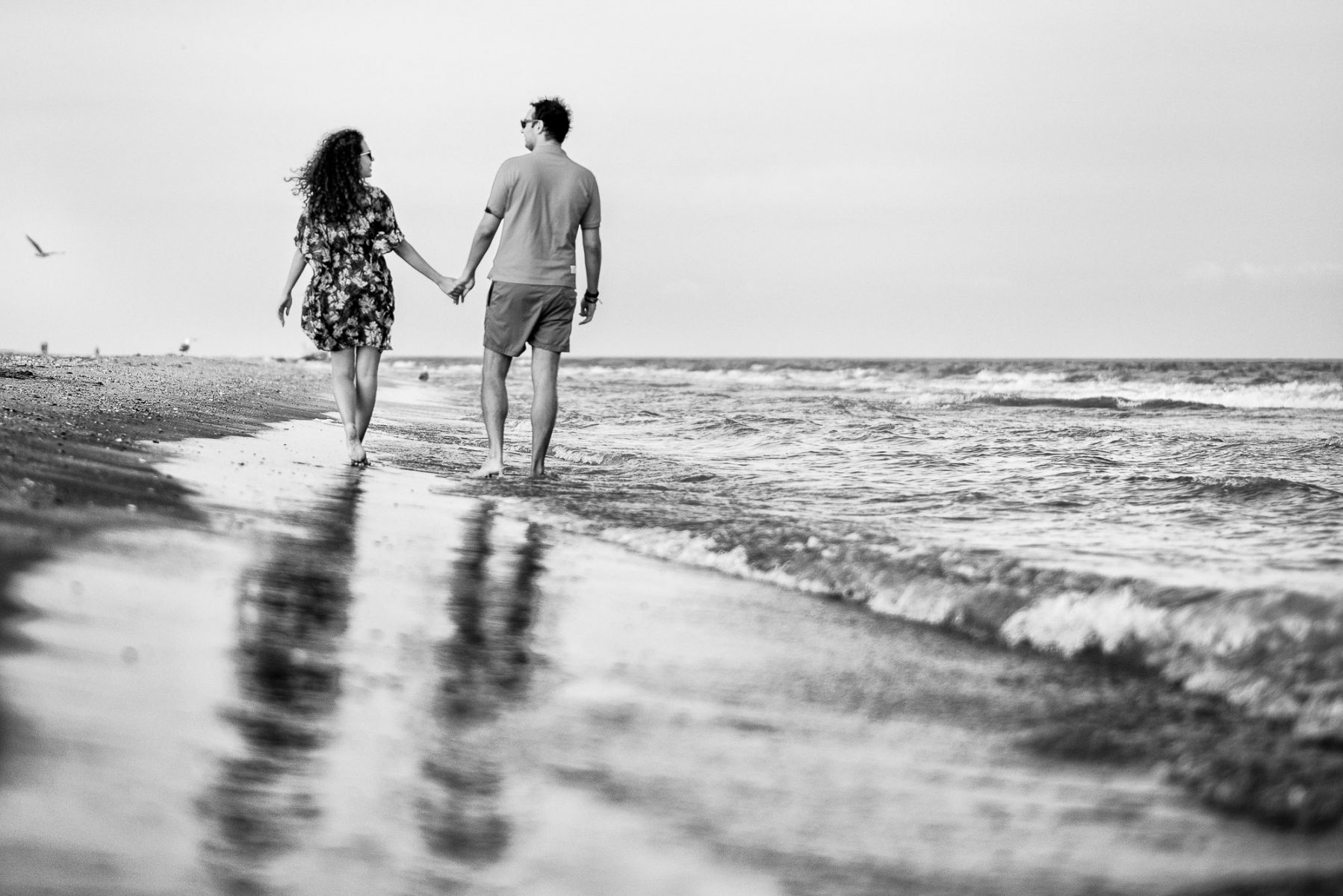 Couple walking holding hands for a Beach engagement photo shoot