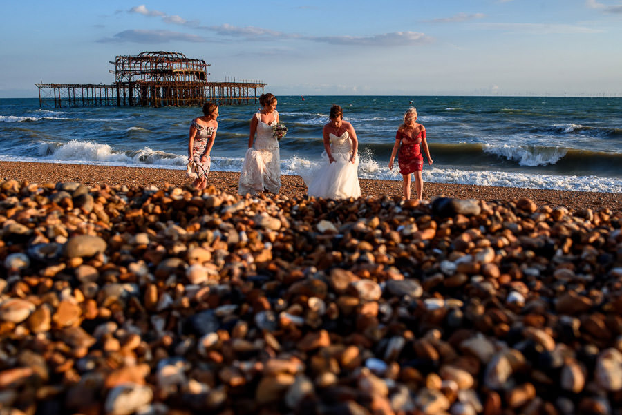 bride and bridesmaids taking wedding photos on Brighton Beach