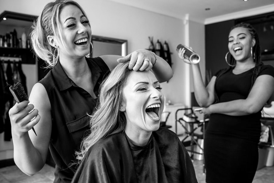 Bride laughing while getting ready for the wedding