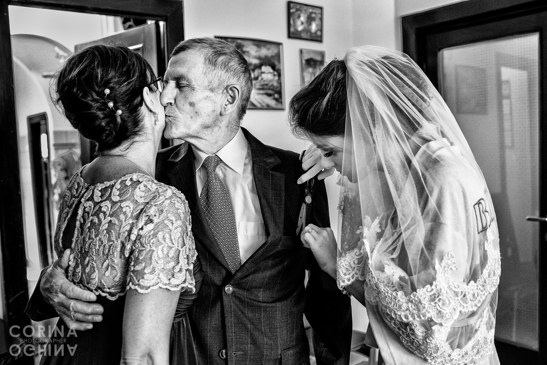 Grandfather kisses mother of the bride, as the bride is helping with his sown pockets