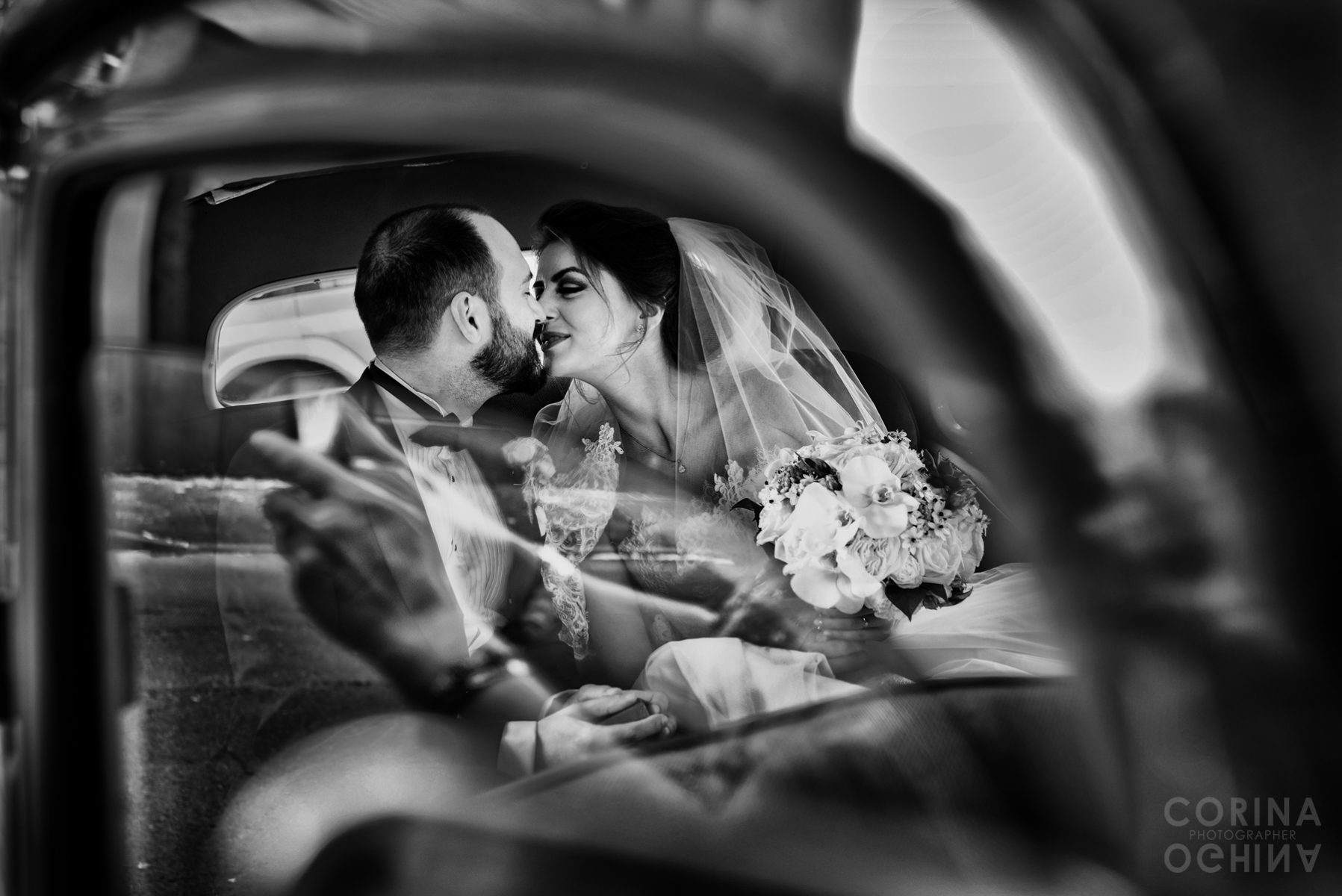 Newlyweds kissing in the car as someone takes a photograph