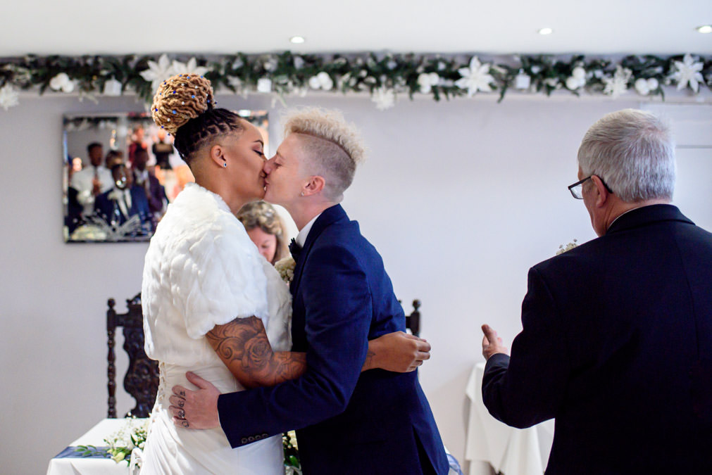 Lesbian couple sharing first kiss as newlyweds