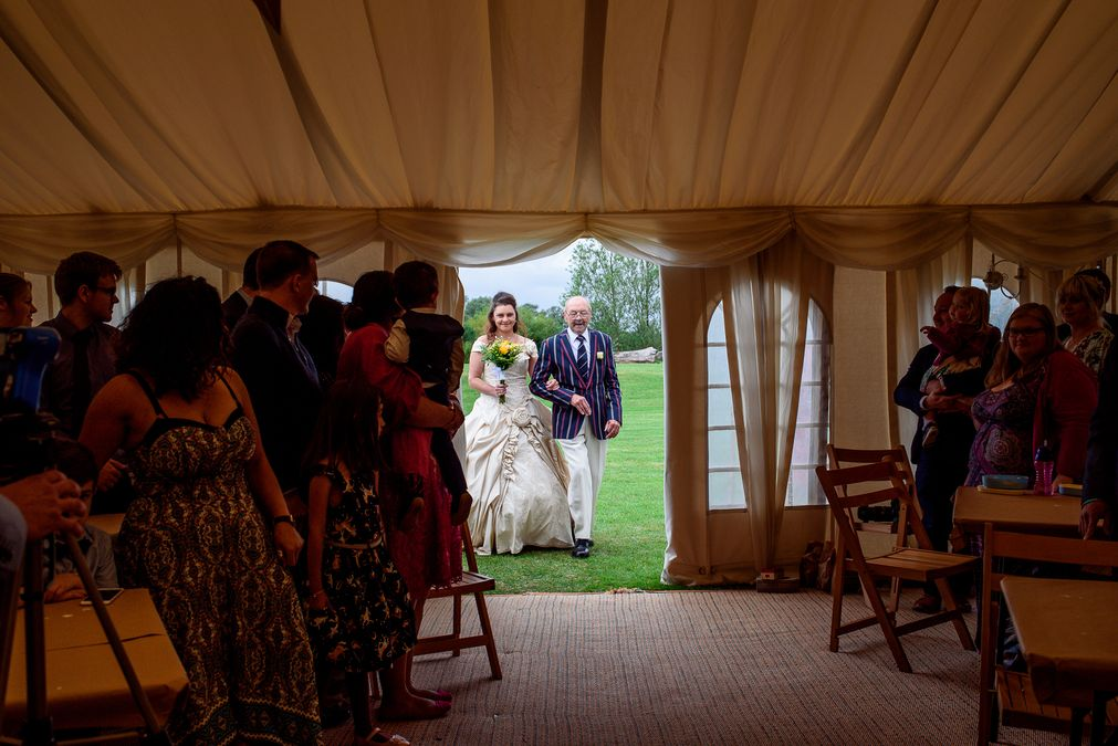 Bride walking down the aisle at Barleylands festival wedding