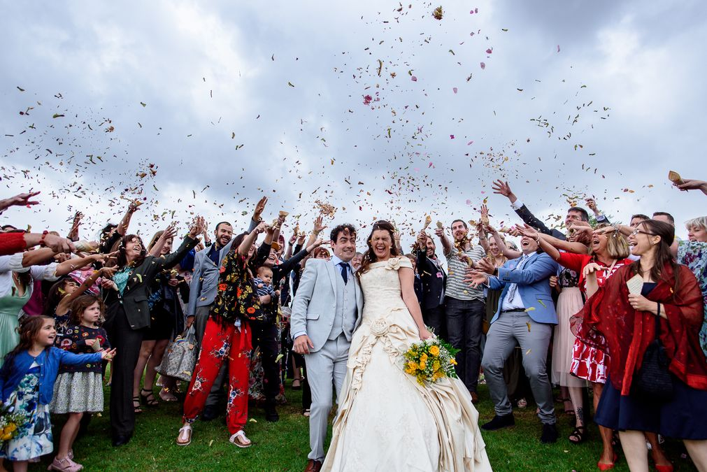 Large group photo of guests throwing confetti at a festival wedding in The Barleylands