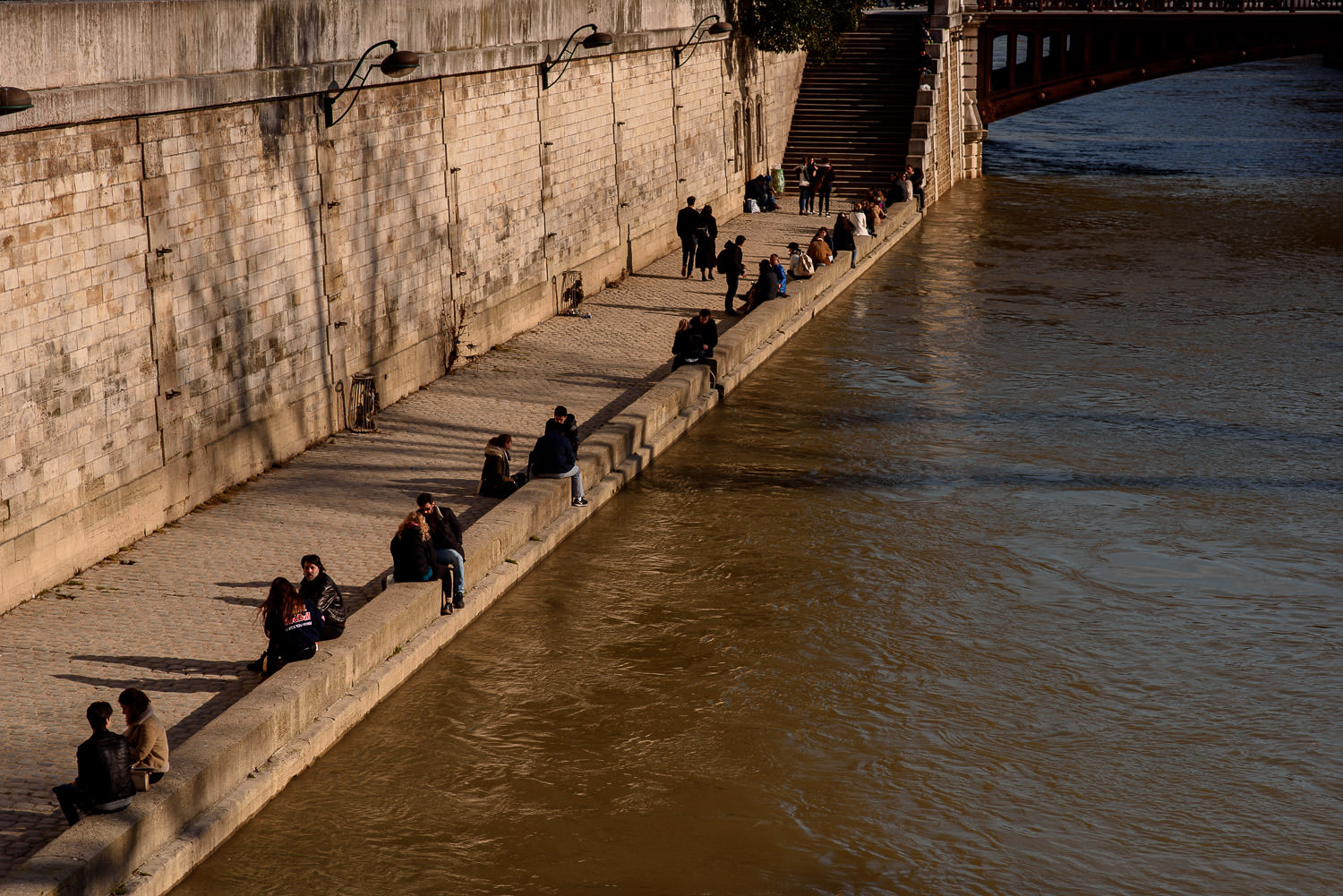 People sunbathing on the banks of river Saine in Paris