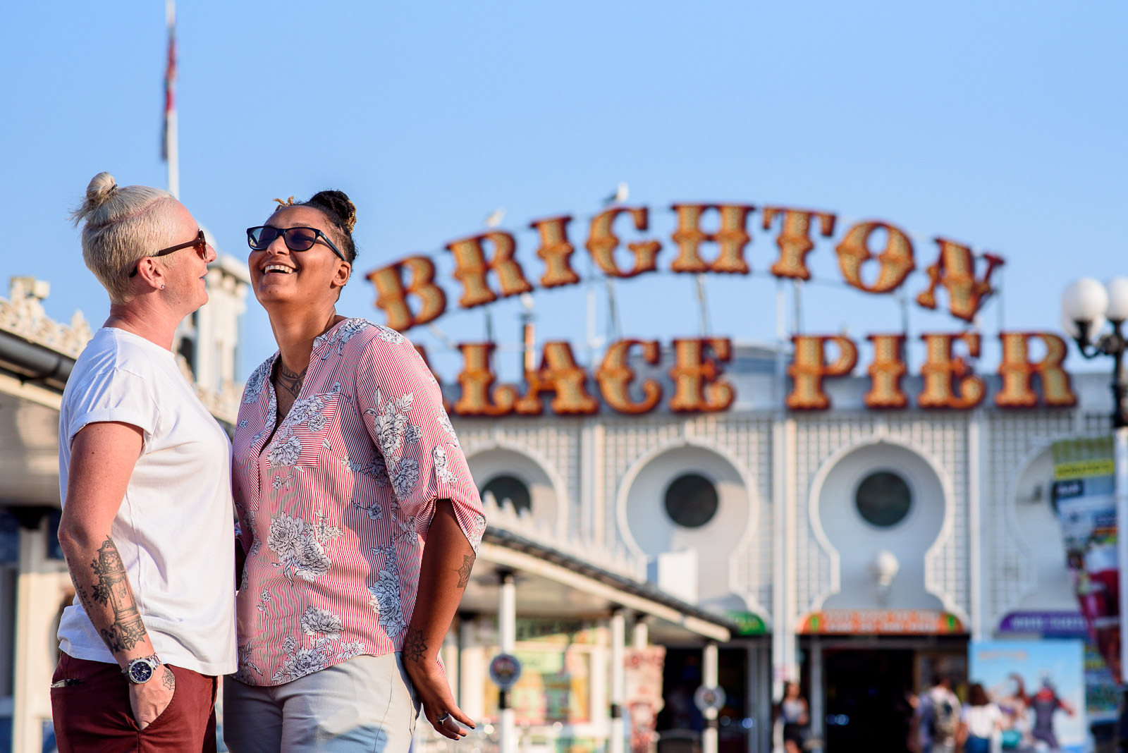 Lesbian couple laughing with the Brighton pier in the background