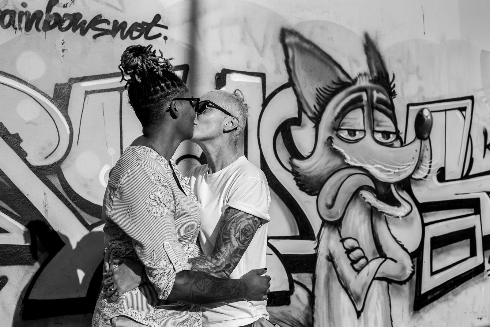 lesbians kissing next to a grafiti