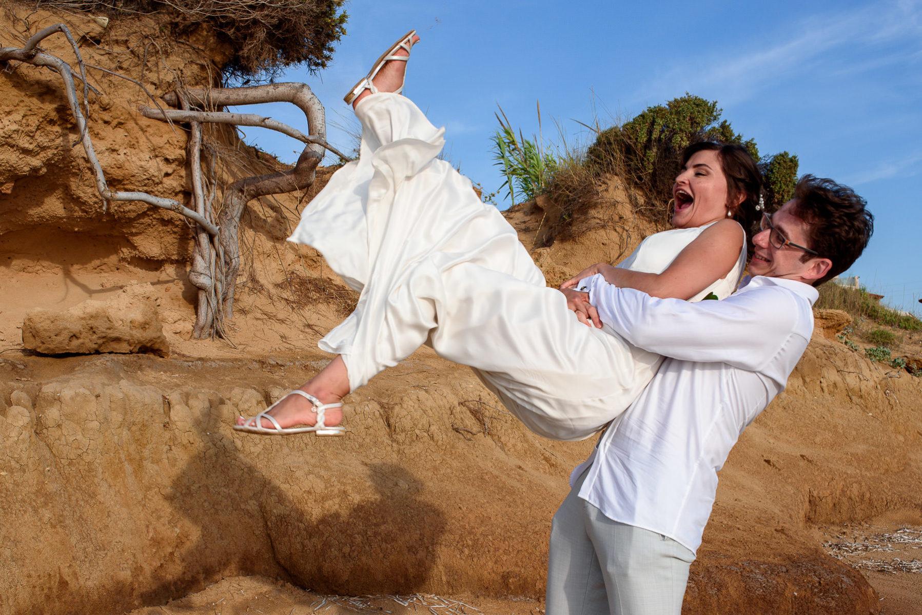 bride and groom having fun on a beach photo shoot