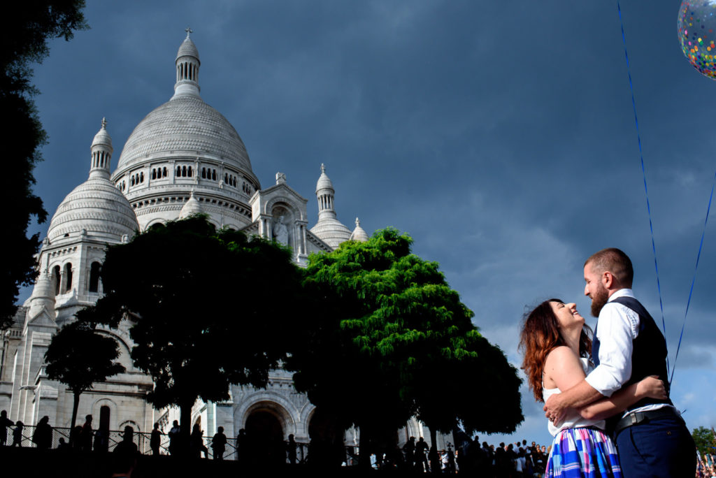 Couple laughing in front of Sacre Coeur on their anniversary photo shoot