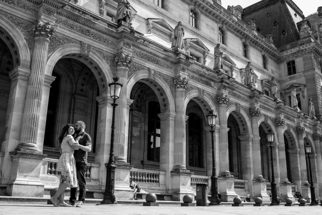 Couple hugging in front of Louvre Museum