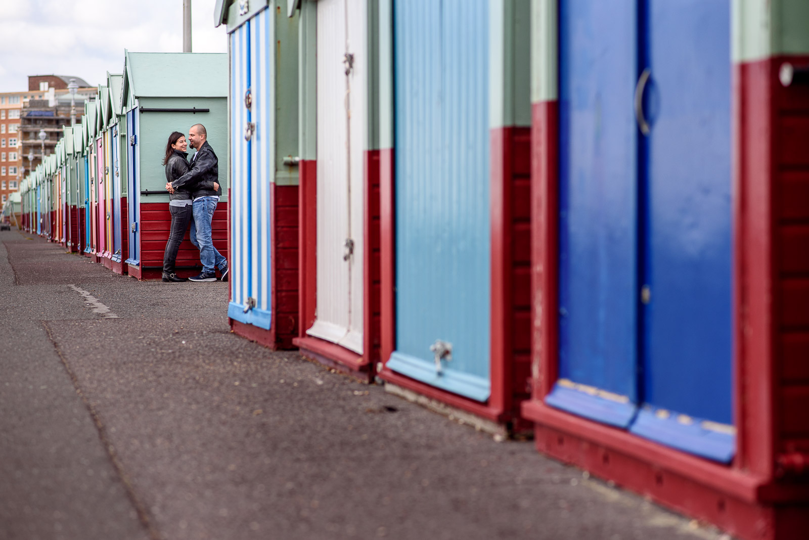 Couple hugging in front of colourful beach huts in Brighton
