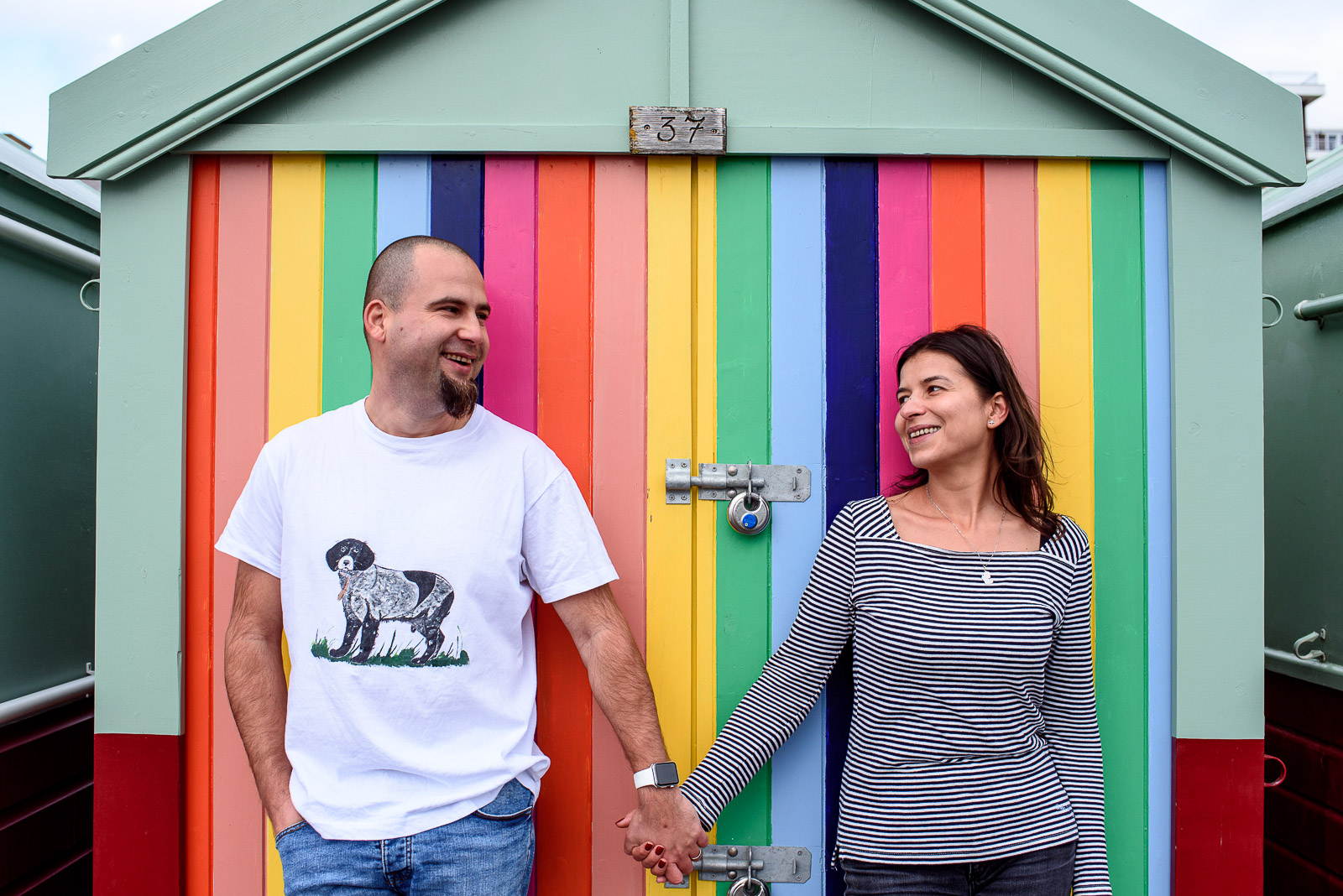 couple holding hands in front of colourful beach huts