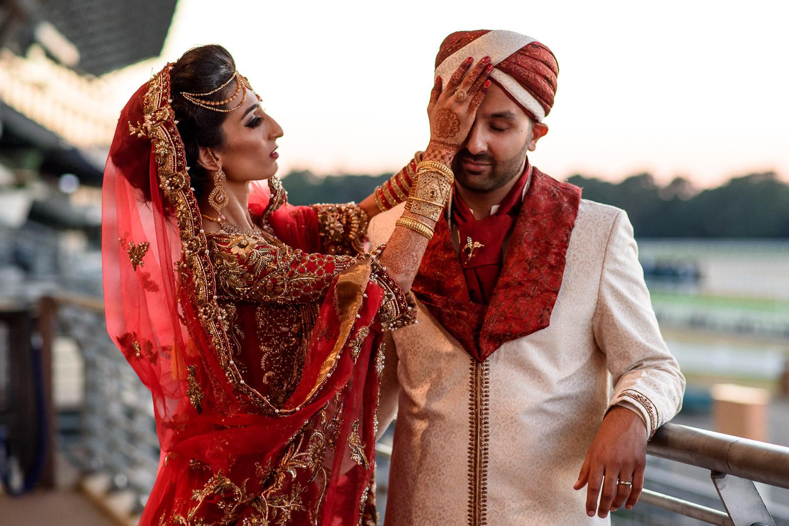 Bride adjusting mehdi dress at indian wedding