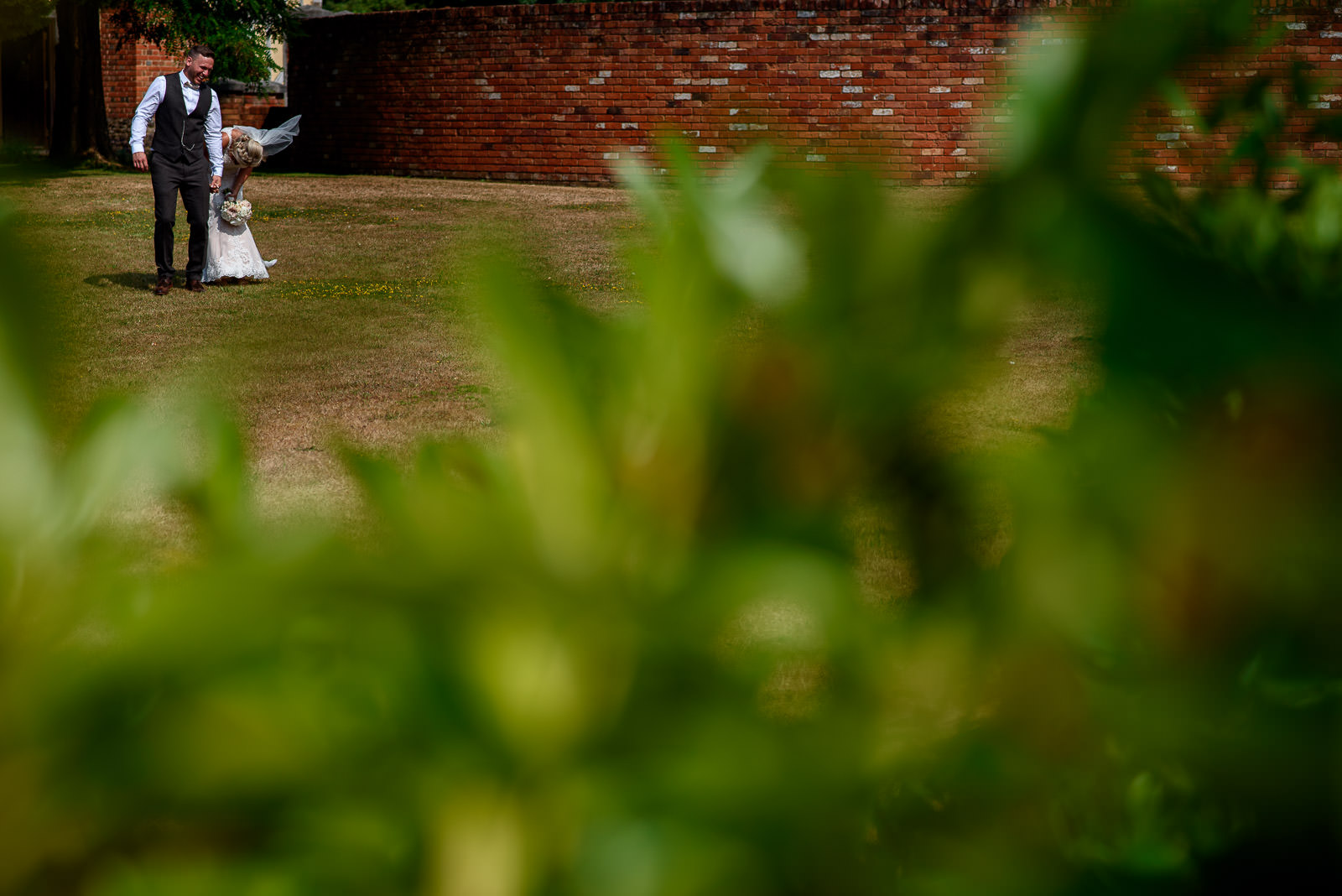 Bride and Groom taking photos outside at Cain Manor