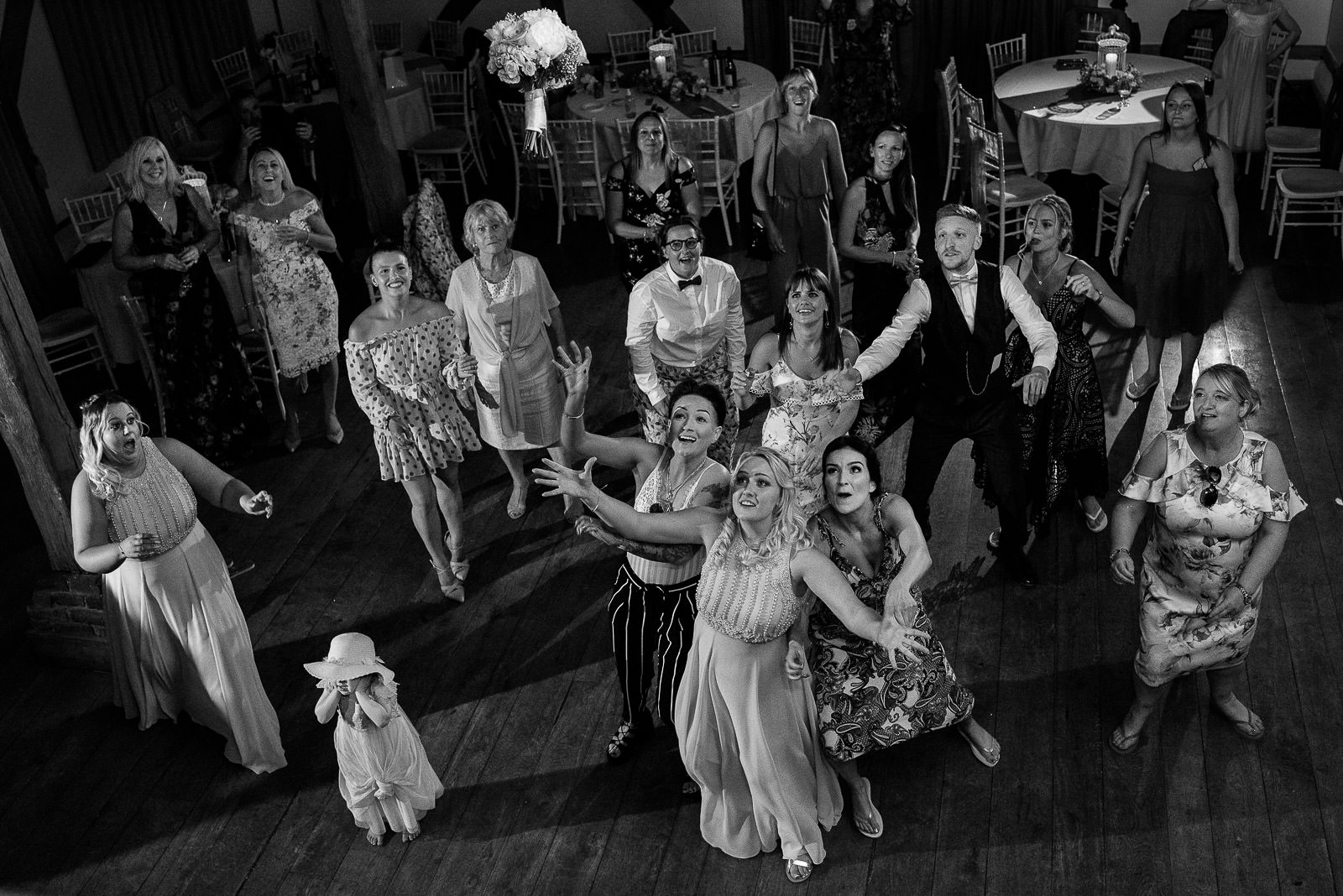 guests fighting to catch the bouquet at wedding in Cain Manor Hampshire