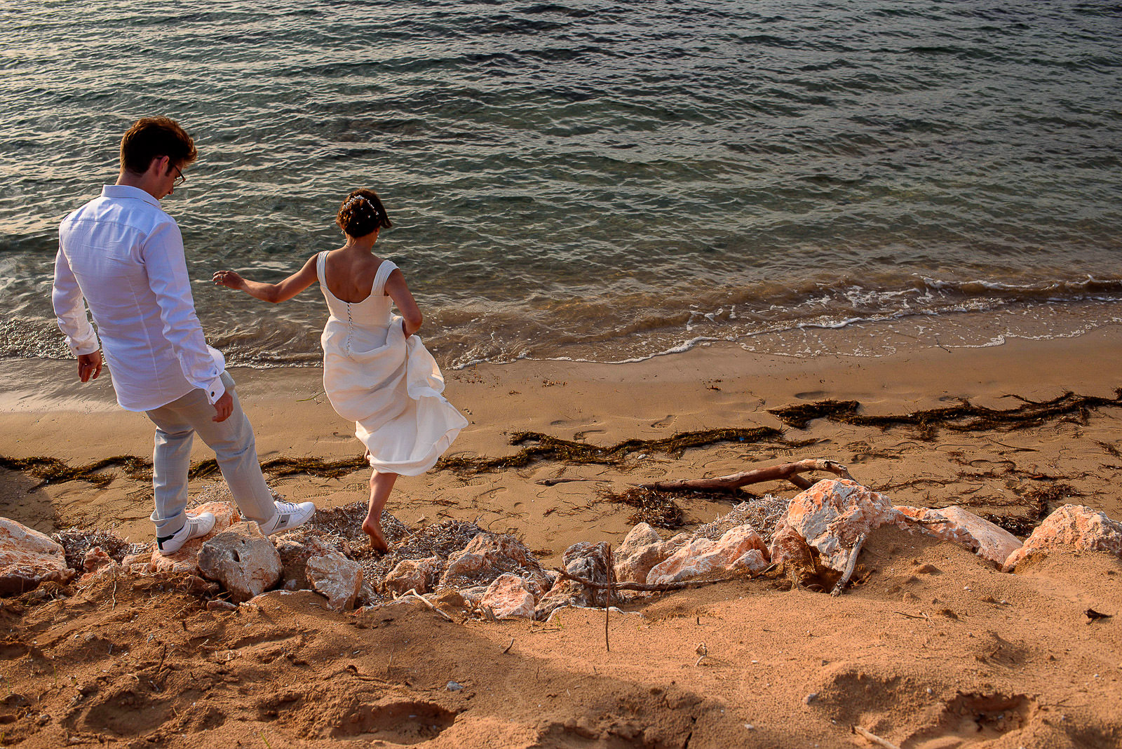Bride and groom running on beach on destination wedding in Greece