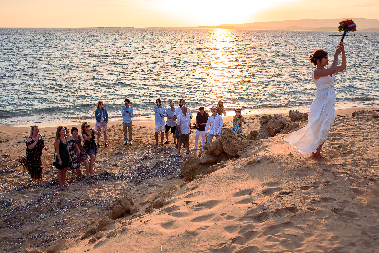 Bouquet toss at a beach wedding