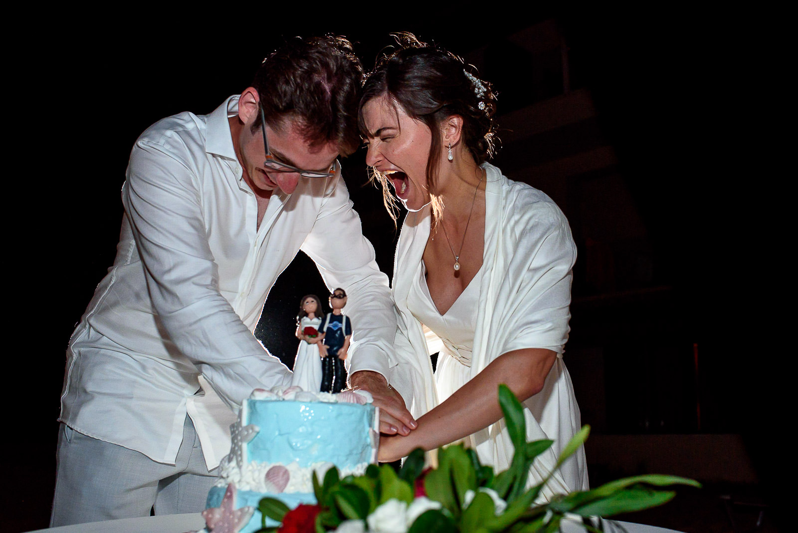 couple cutting the cake at a fun beach wedding