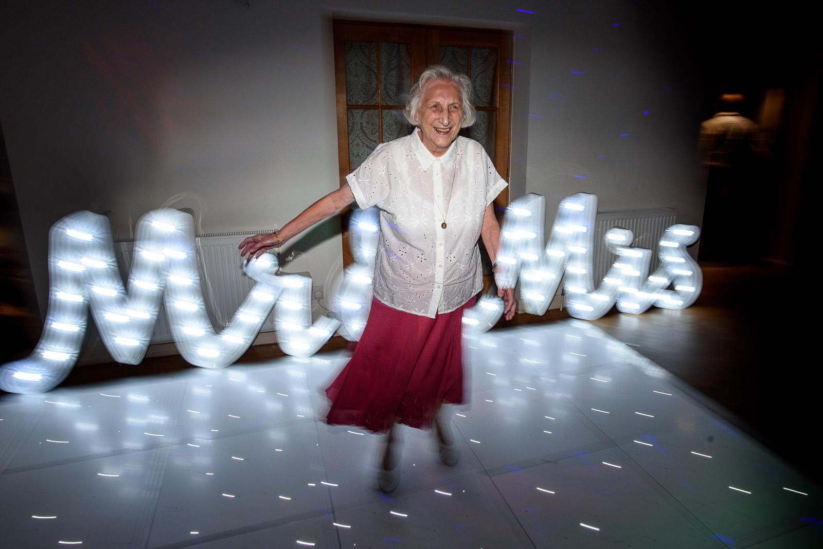 grandmother of the groom dancing at their wedding in Oaks Farm Weddings Croydon