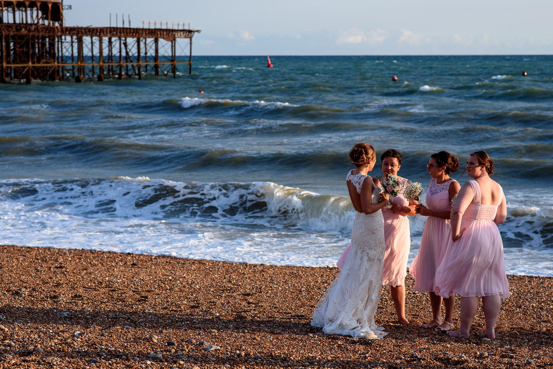 Bride taking photos with Bridesmaids on Brighton Beach