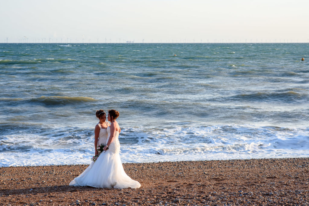 Brides hugging on Brighton Seafront