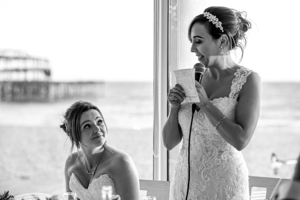Bride smiling at bride during speeches