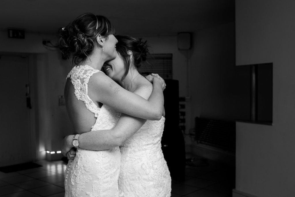 same-sex couple hugging during first dance