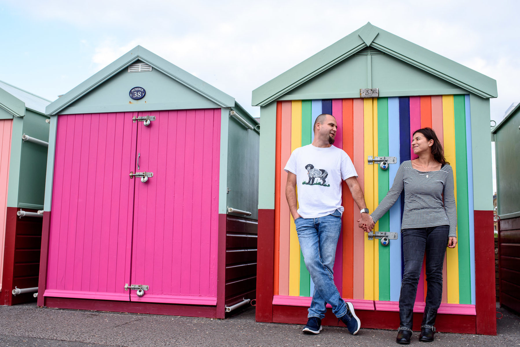 couple holding hands in front of colourful beach huts in Hove