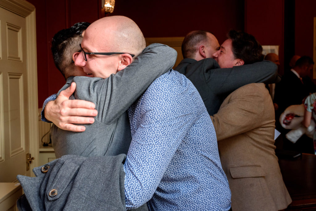 celebratory hugs at a same sex wedding in Brighton