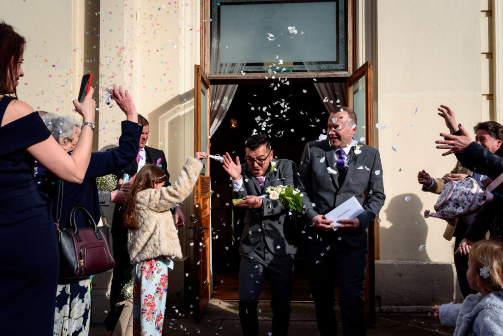 gay couple being showered in confetti to celebrate their wedding in Brighton