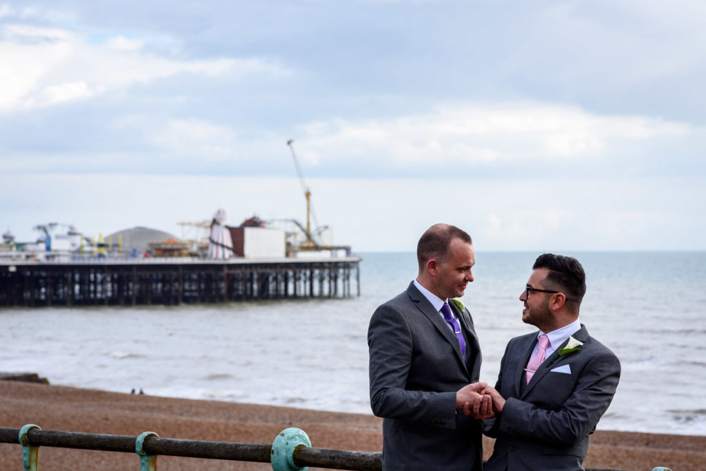 gay couple photo in front of Brighton Pier