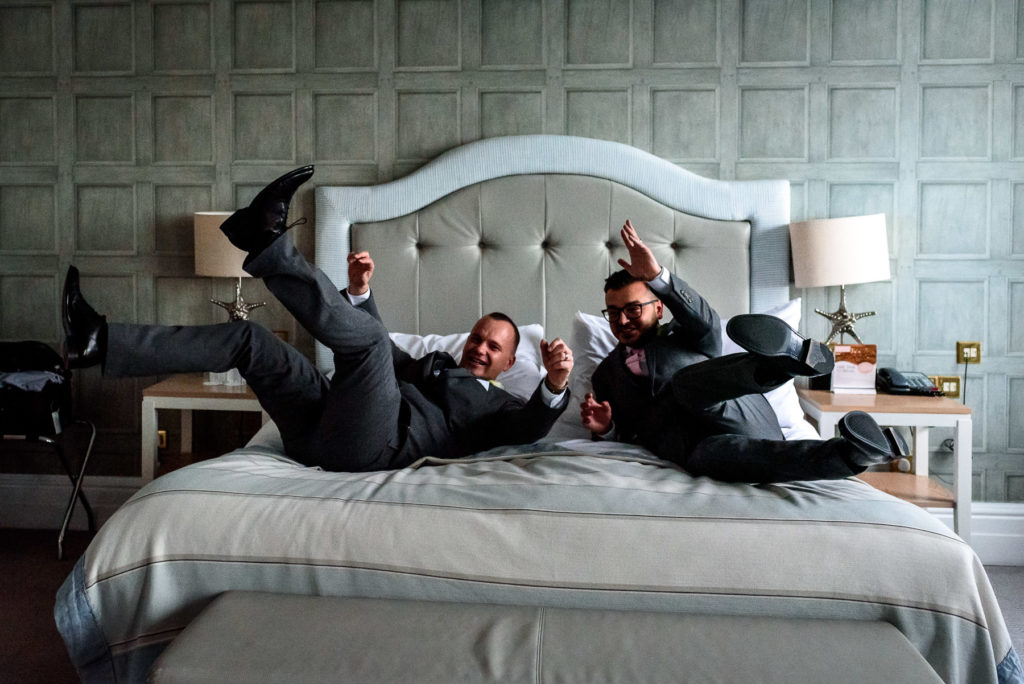 same sex couple jumping on bed at the Grand Hotel in Brighton