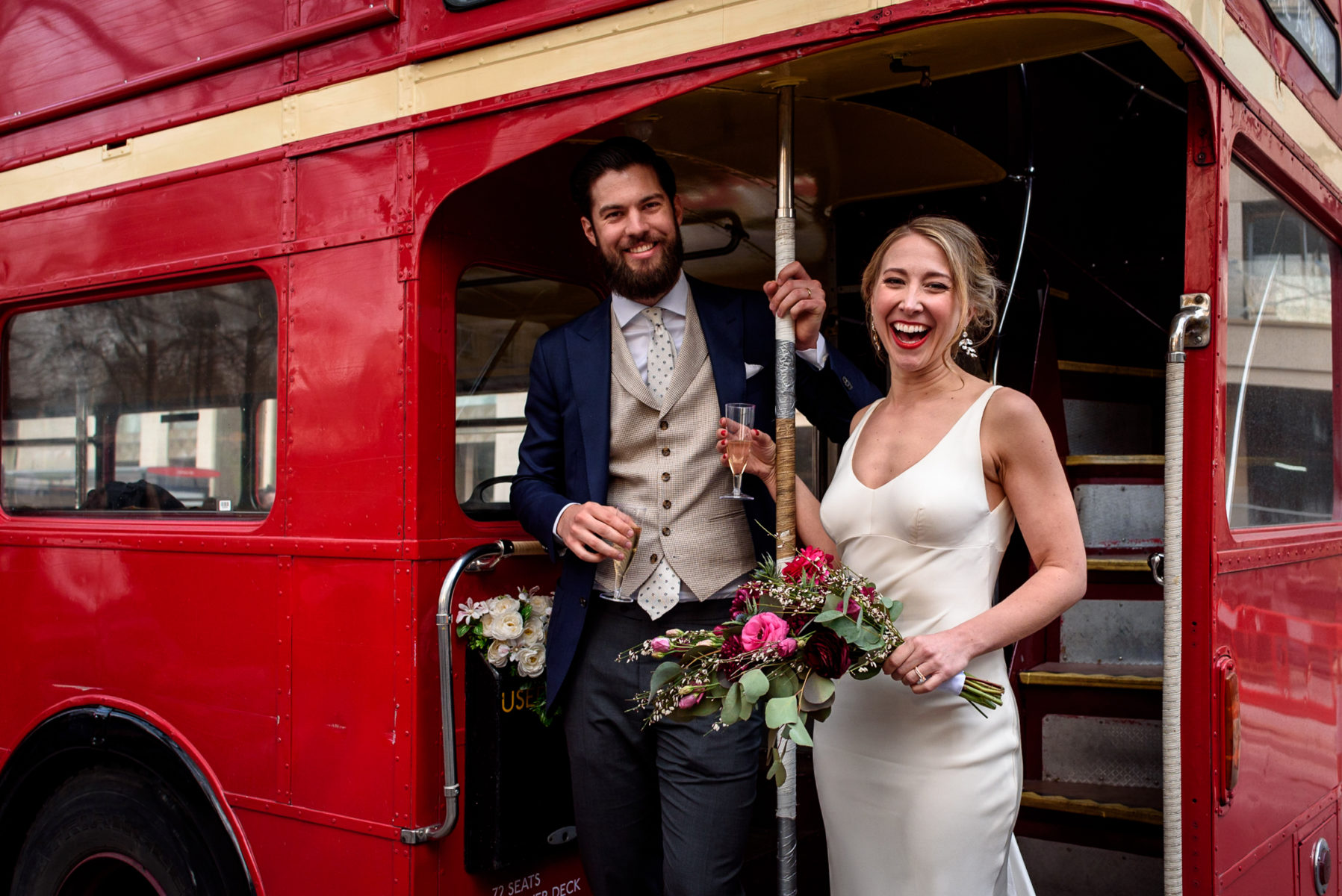couple smiling while boarding a wedding party buss