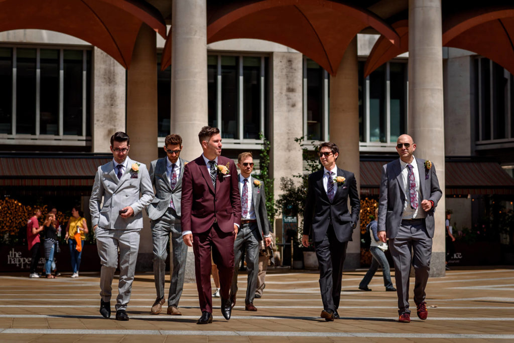 groom and groomsmen walking to St Paul's Cathedral for their weddig