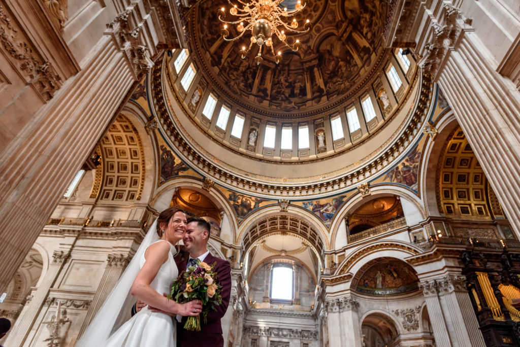 bride and groom taking photos at St Paul's Cathedral after their wedding