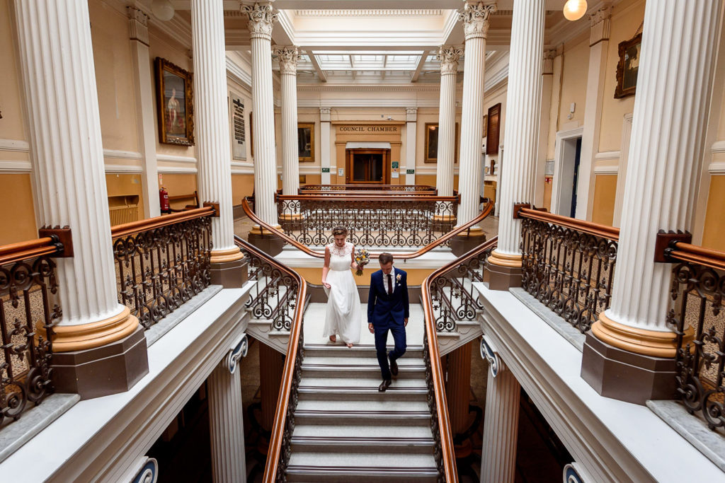 bride and groom walking down the stairs after wedding ceremony at Brighton town hall