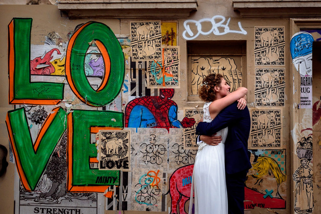 couple hugging while taking wedding photos on graffiti streets in Brighton