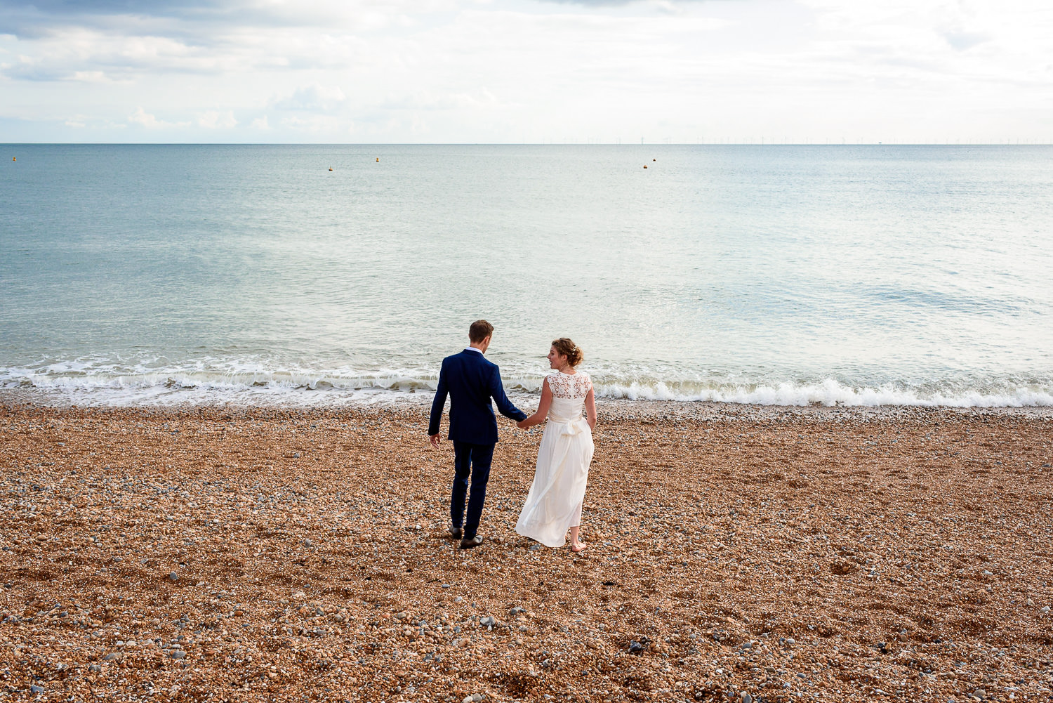 bride and groom taking photos on Brighton Beach