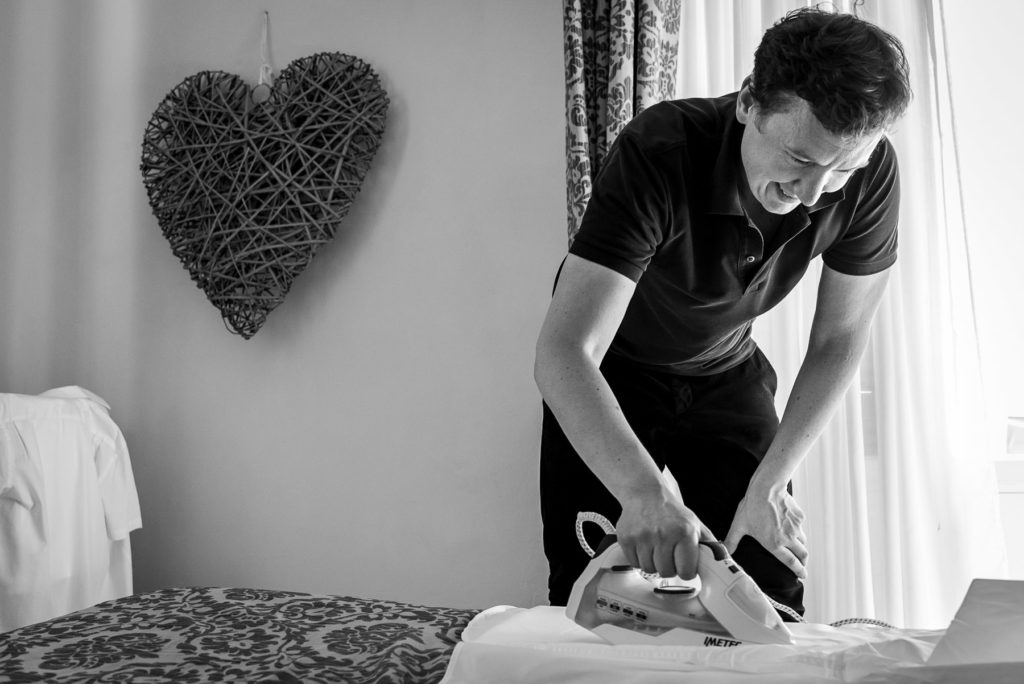 groom ironing his shirt for his wedding day