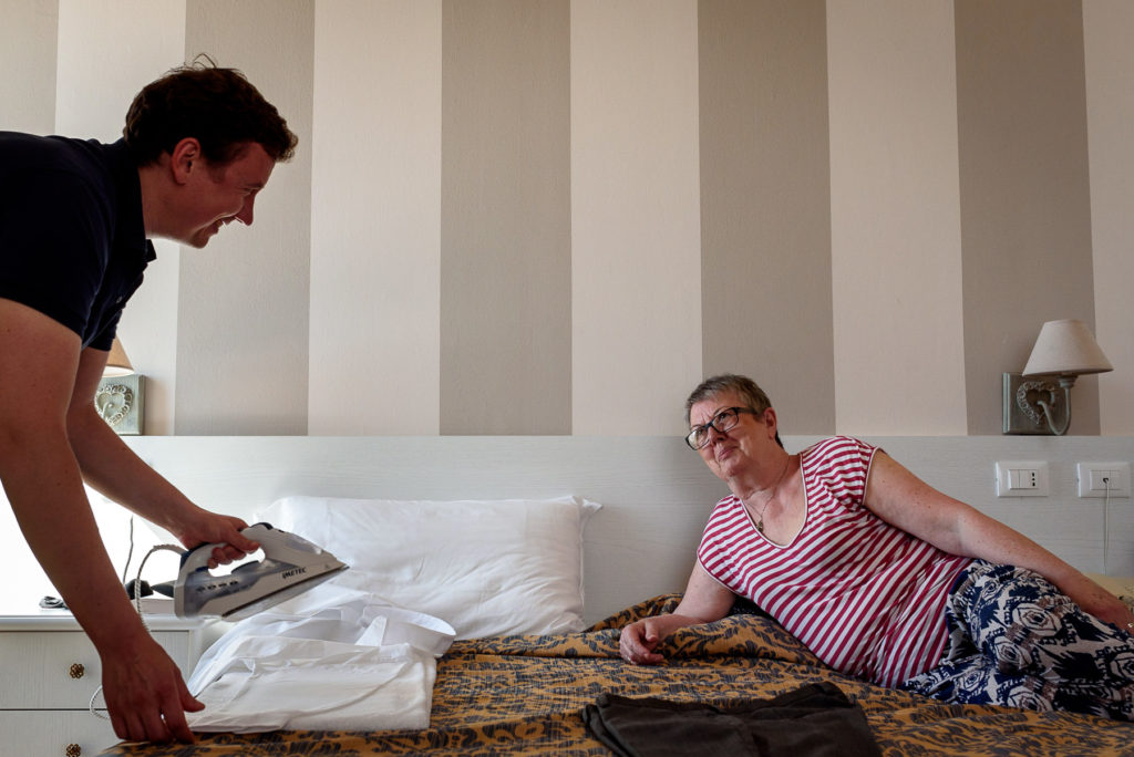 groom ironing his shirt in front of his mum