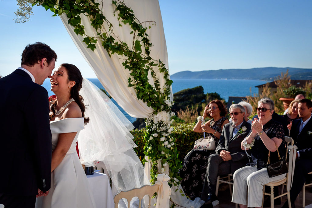 couple laughing during wedding ceremony at Villa Parisi in Castiglioncello