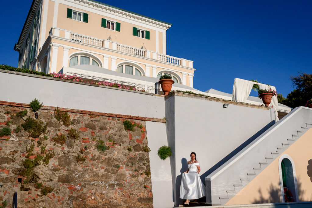 Bride walking down the stairs for her wedding at Villa Parisi in Castiglioncello Italy