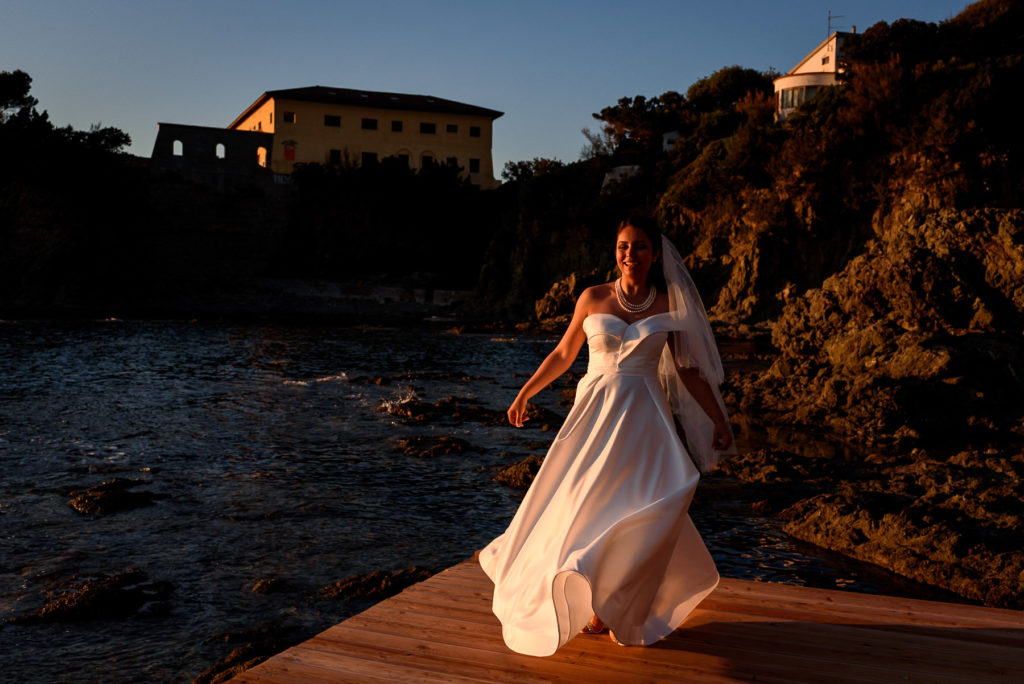 bride playing with her dress on a beach in Castiglioncello