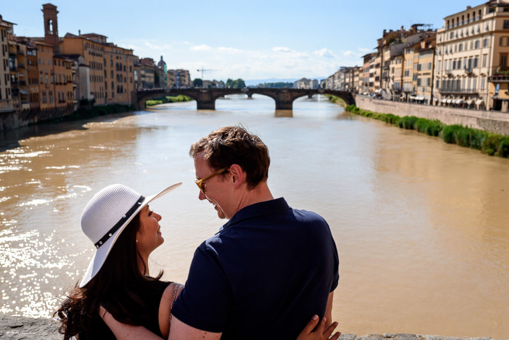 couple taking engagement photos on bridge in Florence