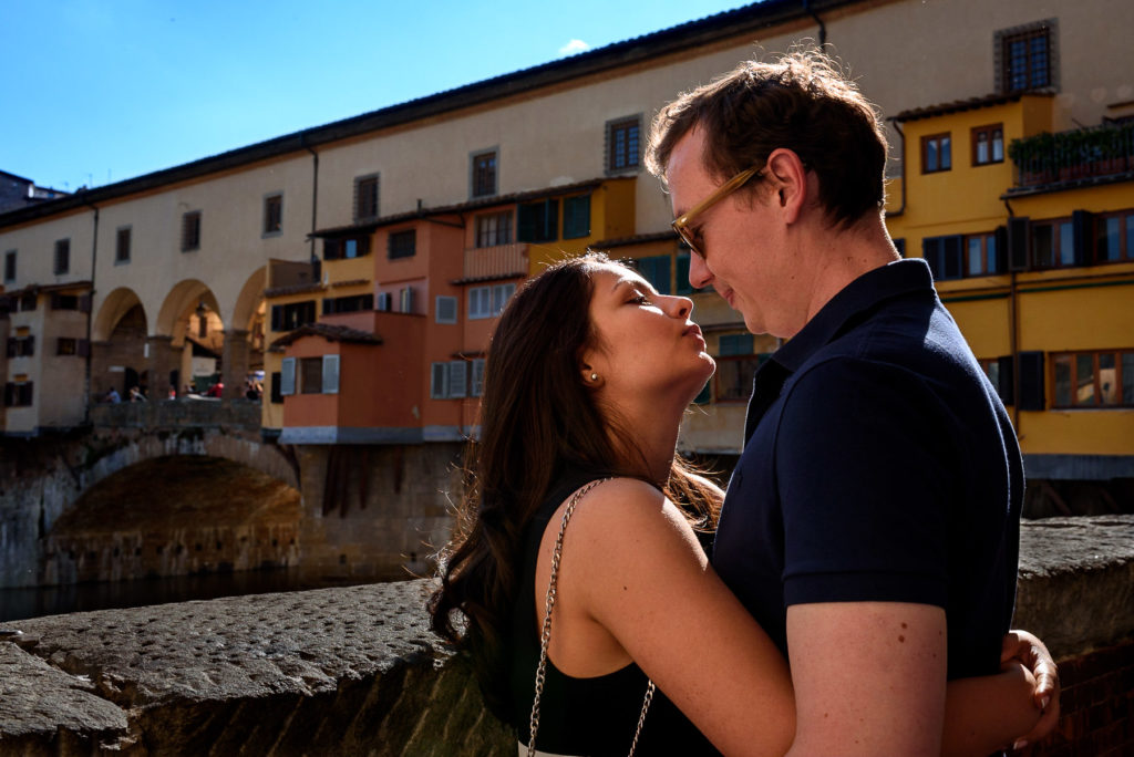 couple kissing in front of Ponte Vecchio on their engagement photo shoot in florence