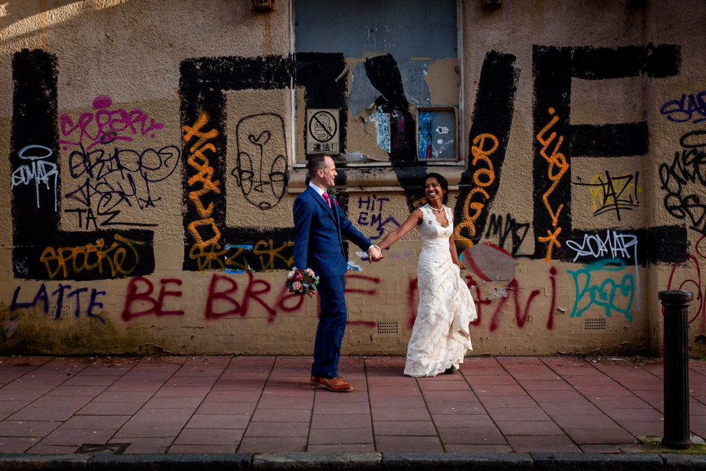 couple posing with graffiti wall in Brighton