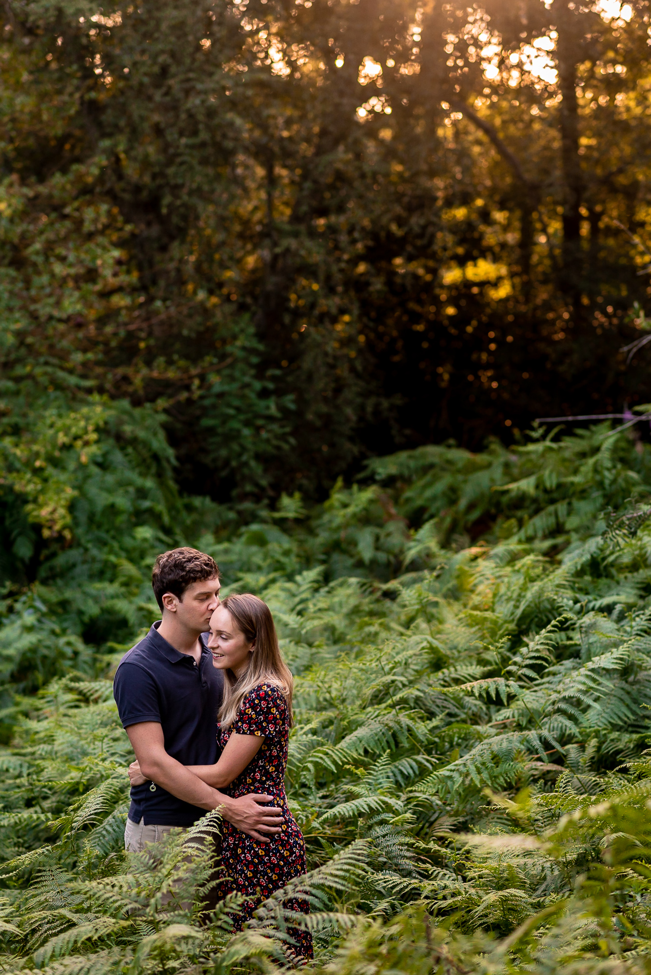 couple hugging in a forest in middle of ferns