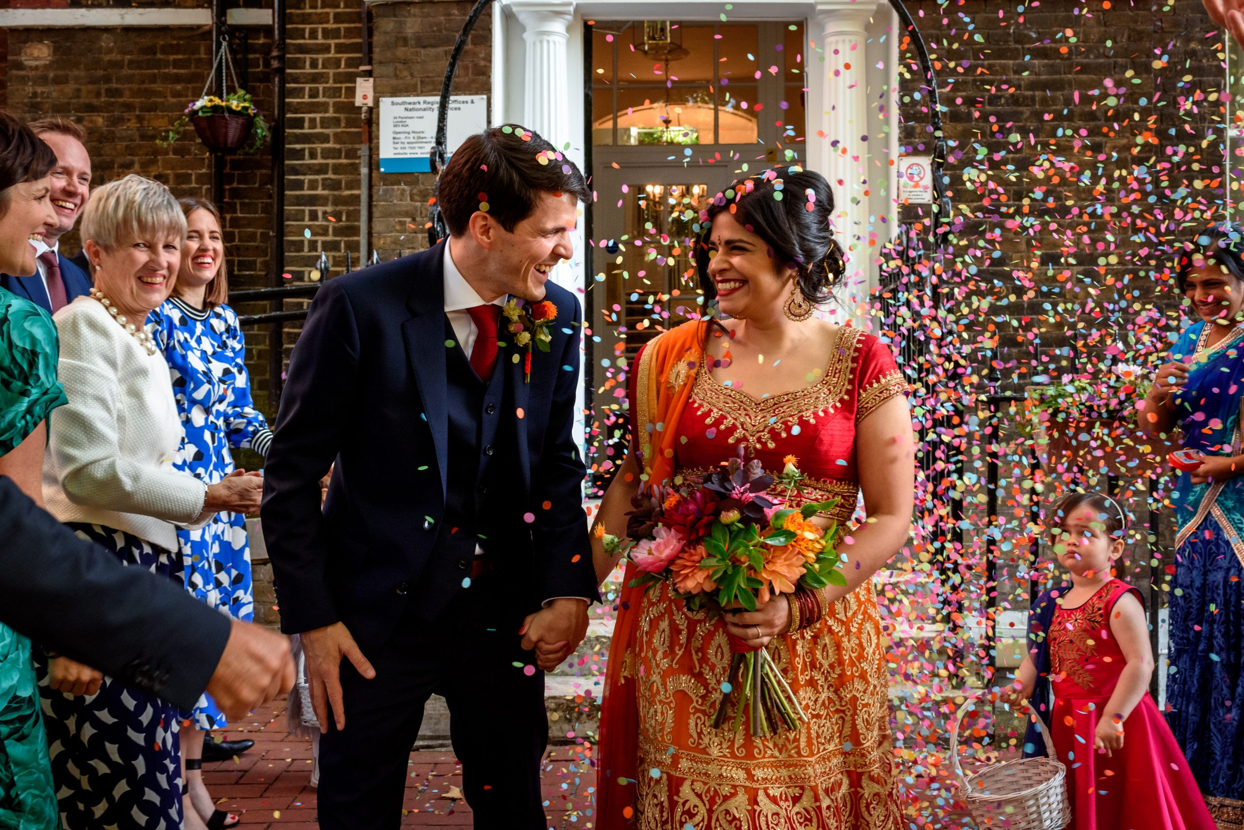 wedding couple with colourful confetti in front of Southwark Registry Office